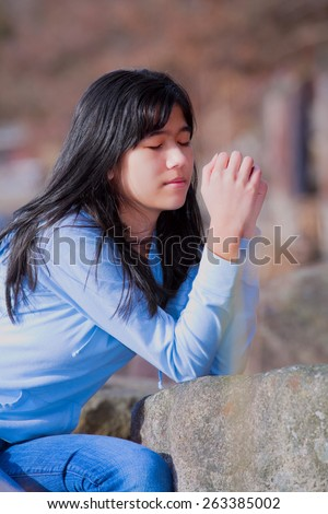 Young biracial teen girl in blue shirt and jeans quietly sitting outdoors leaning on rocks praying - stock photo