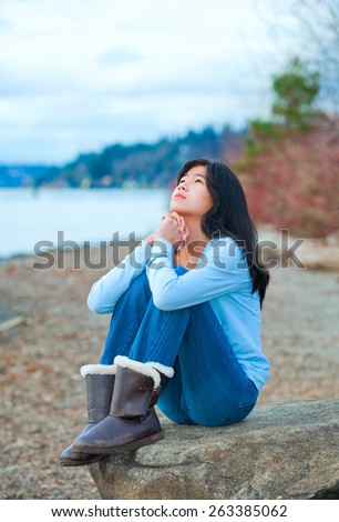 Young biracial teen girl in blue shirt and jeans sitting on boulder or rock  along lake shore praying, face upward to sky - stock photo