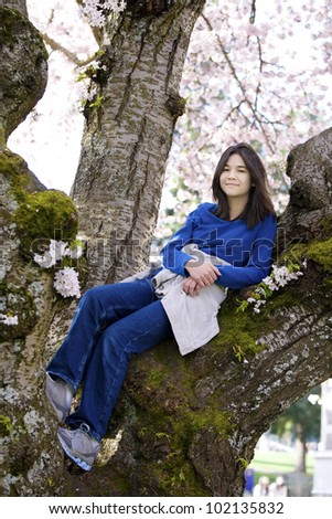 Young biracial teen girl sitting in cherry tree in full bloom