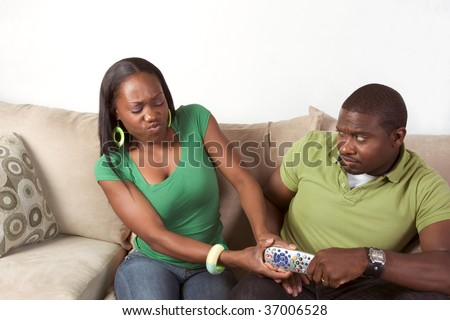 Young black African American couple sitting in living room on couch and arguing over television remote control