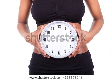 Young black african american woman holding a clock in front of her belly, isolated on white background - African people - stock photo