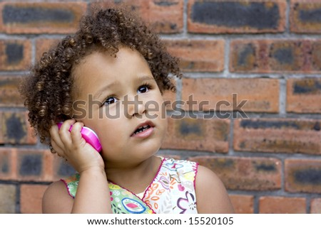 Young black baby girl talking on a toy cell phone - stock photo