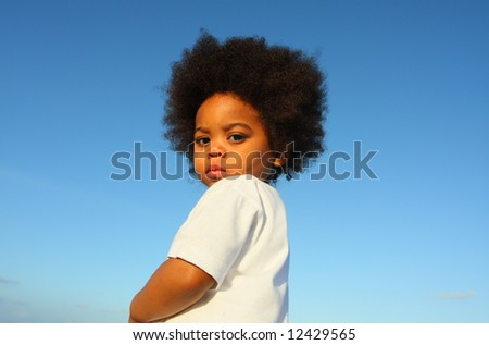 Young black boy with blue sky background - stock photo
