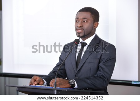 Young black businessman giving presentation to his colleagues - stock photo