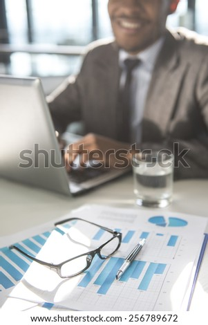 Young black businessman is sitting at the table and working, in modern office. - stock photo