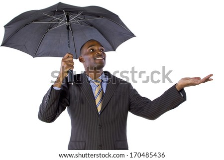 young black businessman looking confident under an umbrella - stock photo