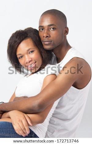 Young Black couple cuddling lovingly - stock photo