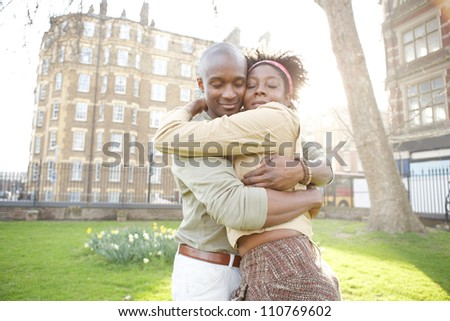 Young black couple hugging in a park at sunset, while visiting London city. - stock photo