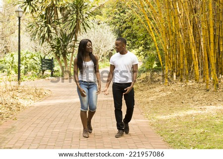 Young Black couple walking down a park path - stock photo