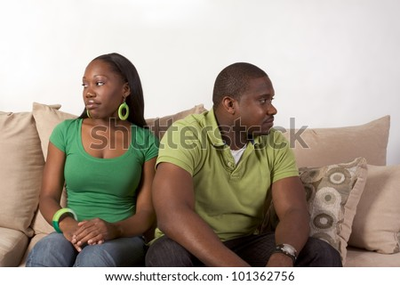 Young black ethnic African-American couple at odds and bad mood not talking with each other and looking away after heated argument