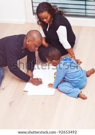 Young black family sitting on the floor drawing a picture with their son. - stock photo