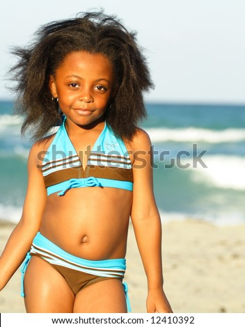 Young black girl posing on the beach - stock photo