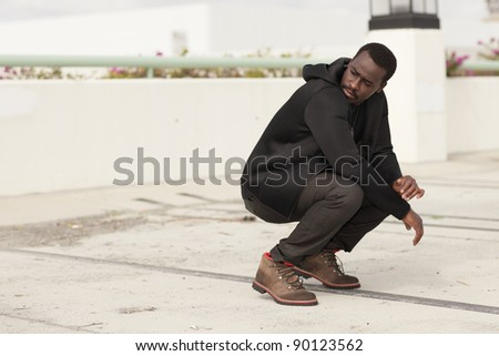 Young black male squatting and looking over shoulder - stock photo