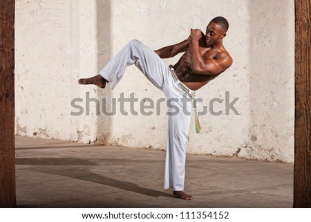 Young Black man demonstrating a knee kick indoors - stock photo