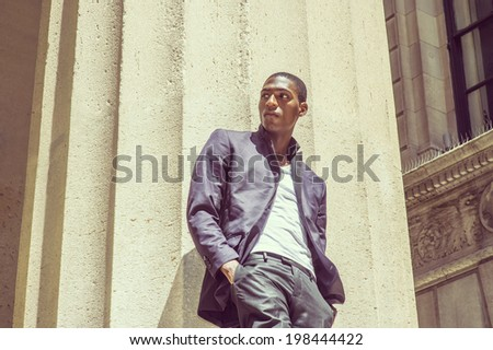 Young black man thinking outside. Wearing a white under wear, fashionable jacket, two hands in pockets, a young black college student is standing under strong sun light, looking around, thinking. - stock photo