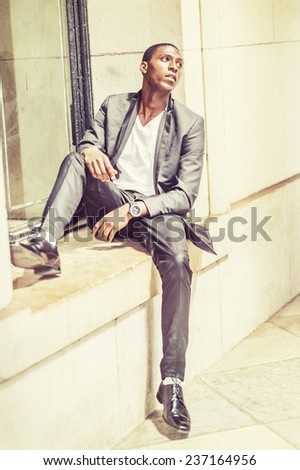 Young black man thinking outside. Wearing white under wear, fashionable jacket, pants, shoes, a young black student is sitting against window frame, sad, emotionally looking up. Street Fashion. - stock photo