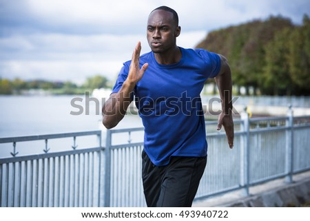 young black man wearing athletic wear running around the lake