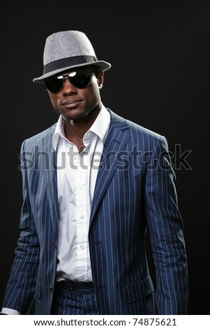 Young black man wearing suit and hat and sunglasses.