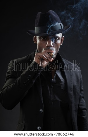 Young black man wearing suit and hat gangster style smoking cigar isolated on dark background. Studio portrait. - stock photo