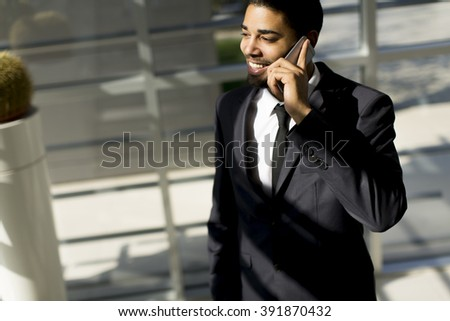 Young black man with telephone in the office