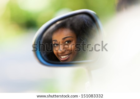 Young black teenage driver seated in her new convertible car - African people - stock photo