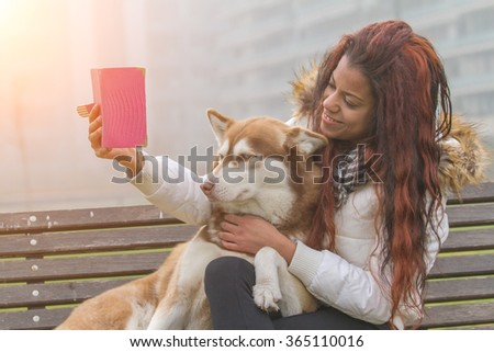 Young black woman and her dog (Siberian Husky) doing selfie  - stock photo
