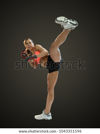 Young black woman fighter kicking isolated on a dark background