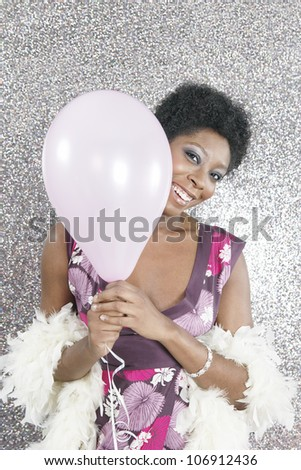 Young black woman holding a pink balloon and smiling at the camera while standing on a silver background. - stock photo