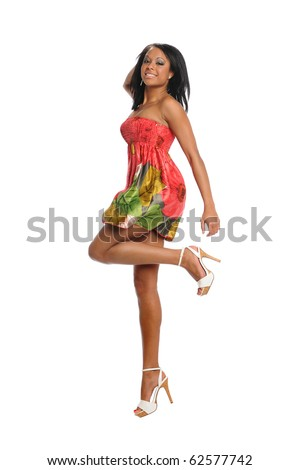 Young black woman jumping wearing a colorful dress isolated on a white background