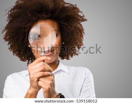 young black woman looking through the magnifying glass