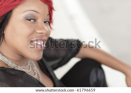 Young black woman sitting and smiling - stock photo