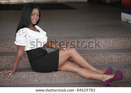 Young black woman sitting with legs crossed
