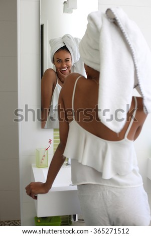 young black woman using body care product in bathroom - stock photo