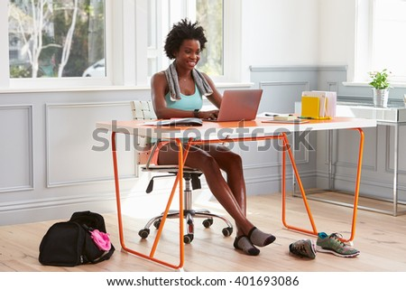 Young black woman using computer at home after exercising - stock photo