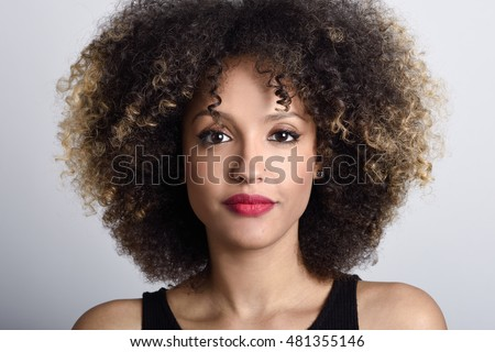 Young black woman with afro hairstyle on white background. Girl with african hairstyle. Studio shot.