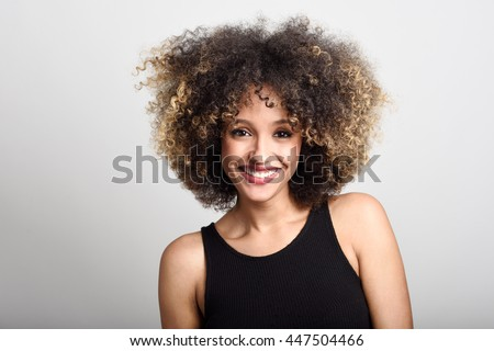 Young black woman with afro hairstyle smiling. Girl wearing black dress. Studio shot. - stock photo