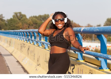 Young black woman with earphone on the street