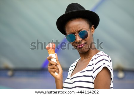 young black woman with hat, sunglasses and striped shirt eating ice-cream, very happy somewhere in the city
