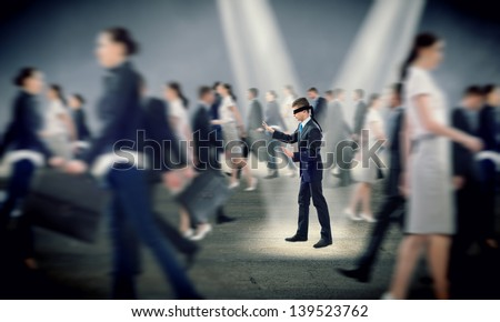 young blindfolded man. his arms and looking for a way out - stock photo