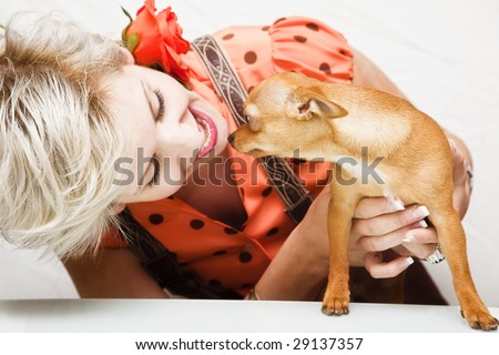 Young blond beauty playing with her pet. - stock photo