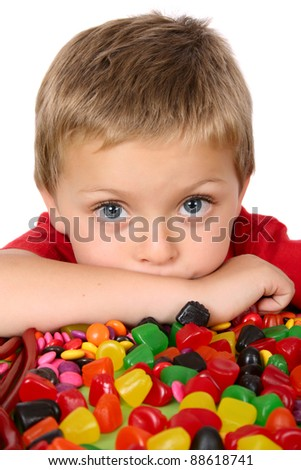 Young blond boy in front of a table filled with sweets - stock photo