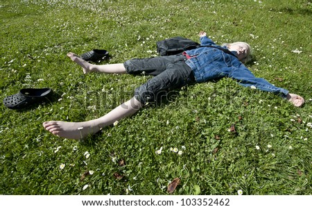 Young blond boy taking a breather on a lawn full of with flower - stock photo