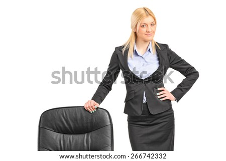 Young blond businesswoman wearing black suit and standing by an office chair isolated on white background - stock photo