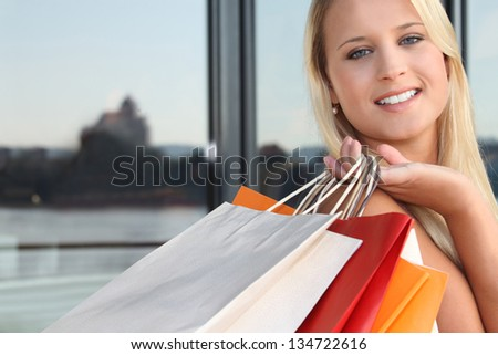 Young blond carrying shopping bags - stock photo