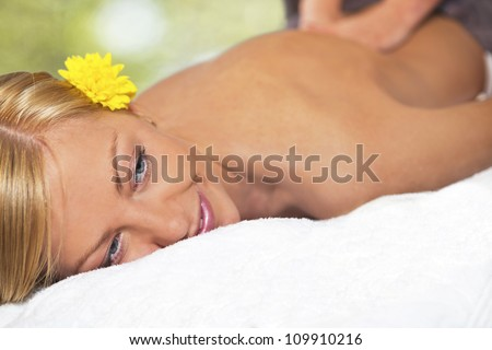 Young blond caucasian woman receiving back massage at Beauty Spa salon. - stock photo