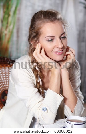 Young blond dreaming girl with tea in the cafe