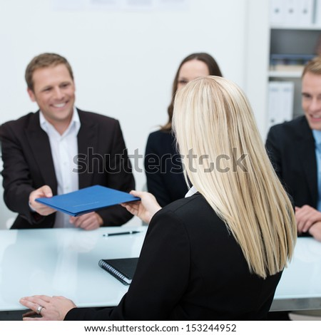 Young blond female job applicant sitting with her back to the camera handing over her curriculum vitae to a smiling businessman conducting the interview