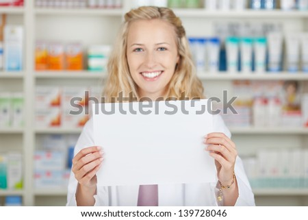 Young blond female pharmacist holding blank paper in pharmacy - stock photo