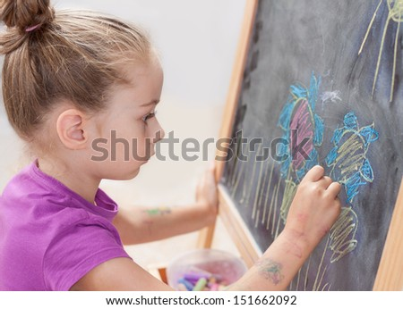Young blond five years old caucasian girl drawing a picture with a chalk on blackboard