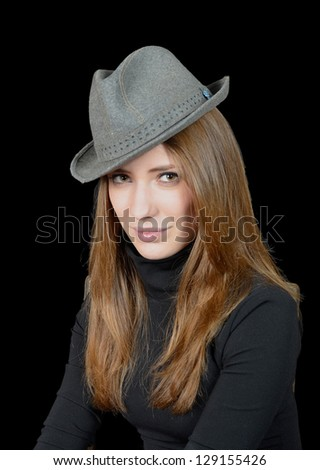 young blond girl in a hat, on a black background - stock photo